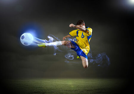 ball lightning: Young football player on stadium in jump taking ball