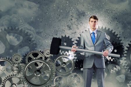 Young determined businessman with hammer and cogwheels at background photo