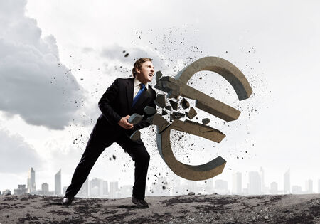 Young businessman breaking stone euro sign  Currency concept photo
