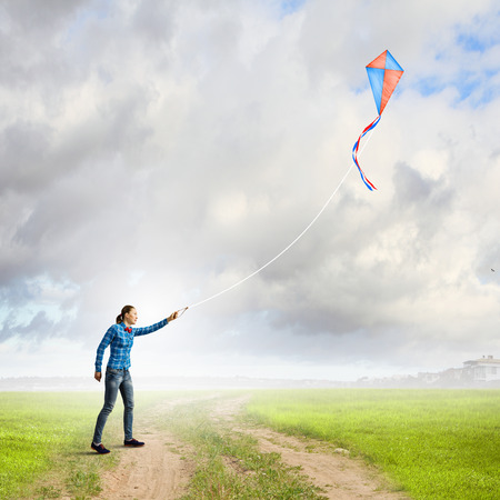 Young woman in casual playing with colorful kite photo