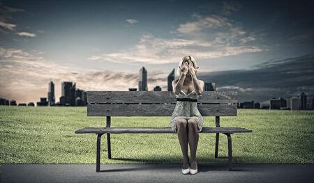 eyes closing: Joven sentado en el banco de ojos de cierre con las palmas