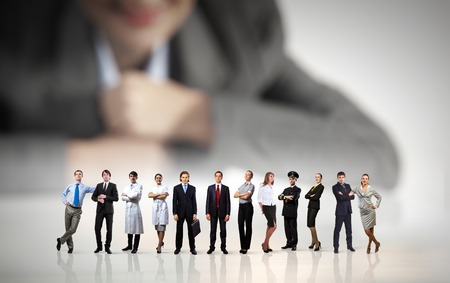 Businesswoman looking at group of businesspeople in miniature photo