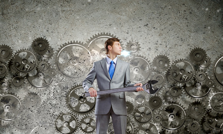 Young determined businessman with wrench in hands and cogwheels at background photo