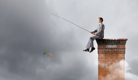 Young businessman sitting on top of building and fishing Stock Photo