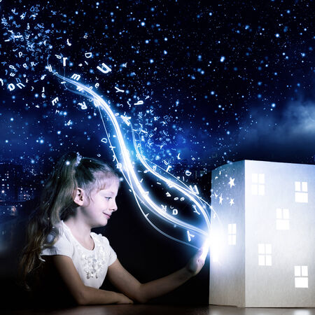 Cute little girl looking at model of house and dreaming photo