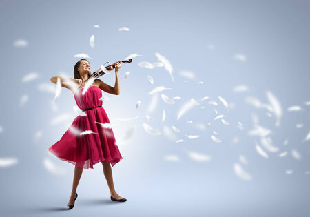 woman violin: Young attractive woman in red dress playing violin