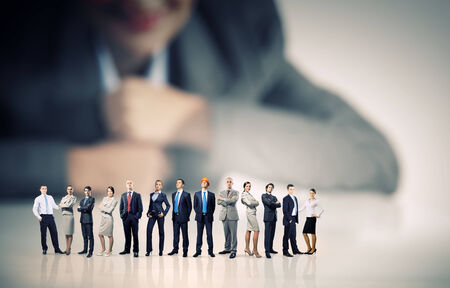 committed: Businesswoman looking at group of businesspeople in miniature