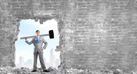 determined: Determined businessman with big hammer in hands