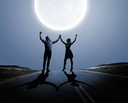 Silhouettes of young couple against full moon photo