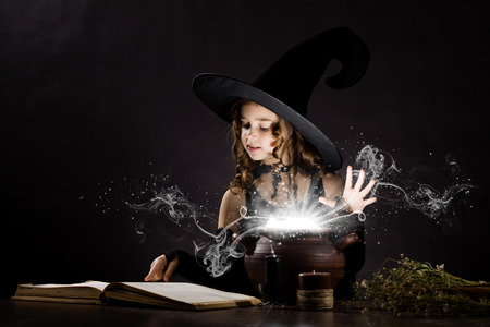 witch hat: Little Halloween witch reading conjure above pot