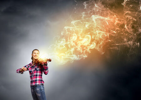 Young pretty woman in casual playing on violin Stock Photo