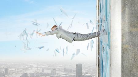 deadlock: Businessman jumping through glass window of office Stock Photo