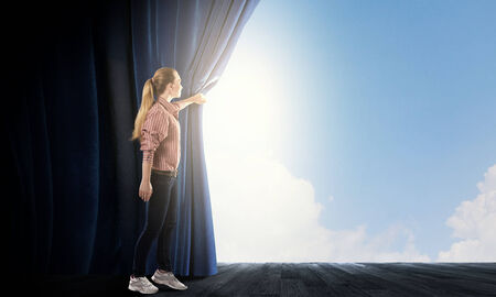 behind scenes: Young woman in casual opening blue curtain and looking at clear sky