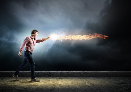 supernatural power: Young man in casual throwing fire ball Stock Photo