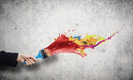 Close up of hand holding brush with colorful paint splashes photo