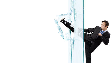 fed up: Young determined businessman breaking glass with karate kick