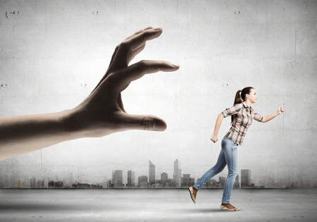 withhold: Young woman in casual escaping from big male hand Stock Photo
