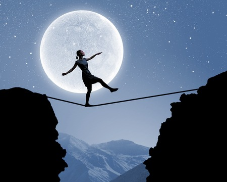 moon walker: Silhouette of woman balancing on rope above gap Stock Photo