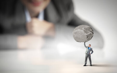 Businesswoman looking at miniature of businessman lifting stone above head photo