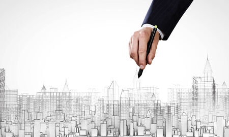 urban housing: Close up of male hand drawing construction project Stock Photo