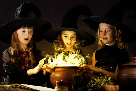 Three little Halloween witches reading spell above pot photo