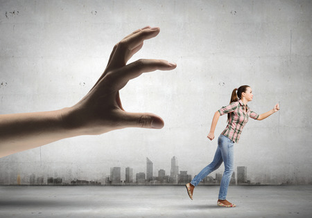 Young woman in casual escaping from big male hand photo