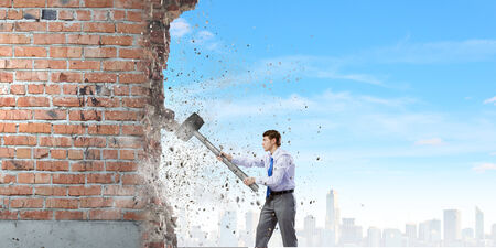 cement solution: Young determined businessman with big hammer in hands crashing wall