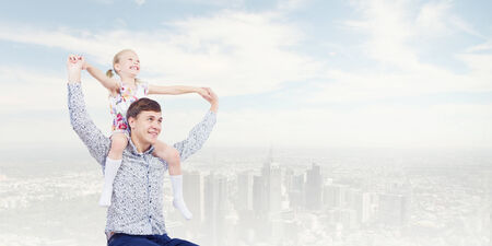 6 7 year old: Little daughter sitting on father s shoulders  Parenting concept