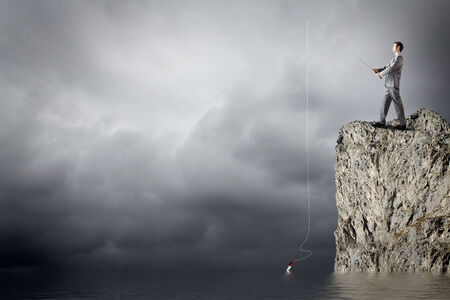 Young businessman standing on top of rock and fishing photo
