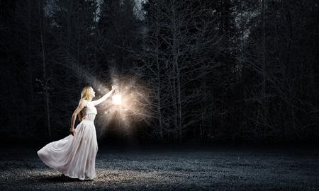 Giovane donna in abito lungo bianco a piedi nella notte di legno Archivio Fotografico - 30275026