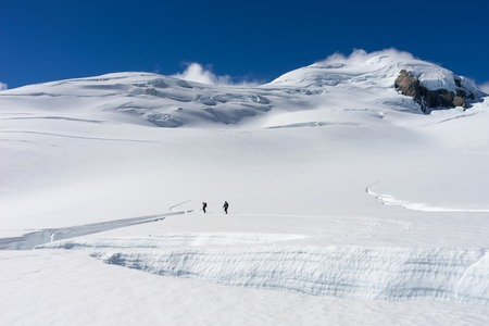 snows: Group of people walking among snows of New Zealand Alps