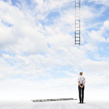 goal oriented: Rear view of businesswoman looking at broken ladder