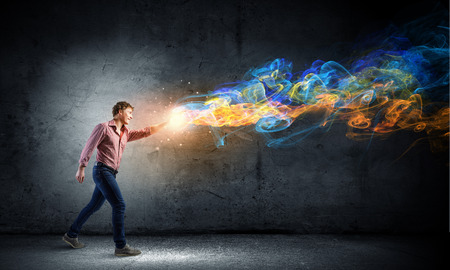 supernatural power: Young man in casual throwing colorful paint splashes