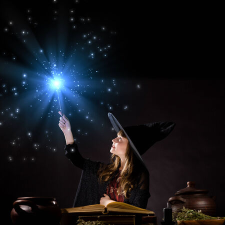 Little Halloween witch making magic with stick photo