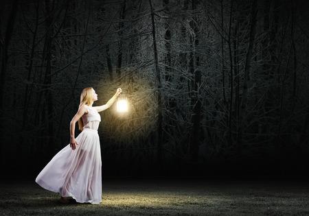 Mujer joven en blanco vestido largo caminar en la noche de madera Foto de archivo - 30275596
