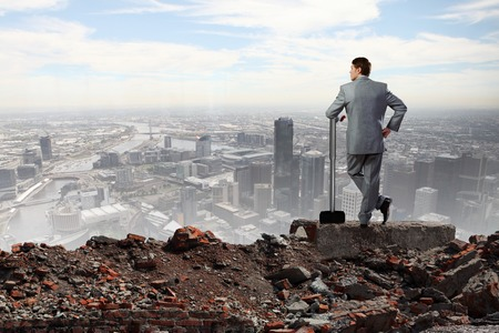 Young determined businessman with big hammer in hands standing on ruins Stock Photo