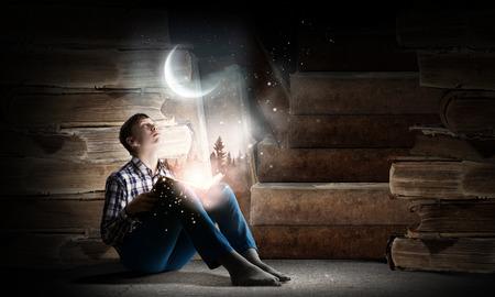 Tiener jongen dragen jeans en t-shirt en een boek lezen Stockfoto