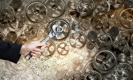 business partner: Close up of businessman hand fixing mechanism with spanner Stock Photo