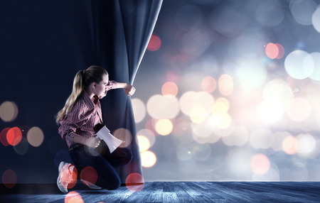 Young girl on stage with megaphone opening blue curtain Stock Photo