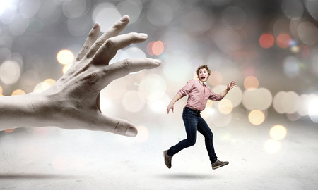 Young man trying to run away from big male hand photo