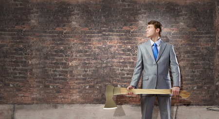 malefactor: Young determined businessman with axe in hands