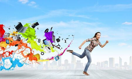 escaping: Young woman in casual escaping from colorful splashes Stock Photo