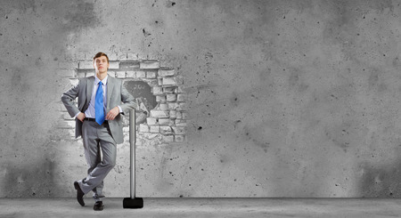 Young businessman breaking cement wall with hammer photo