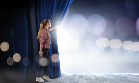 Young woman in casual opening blue curtain