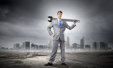 Young determined businessman with wrench in hands photo