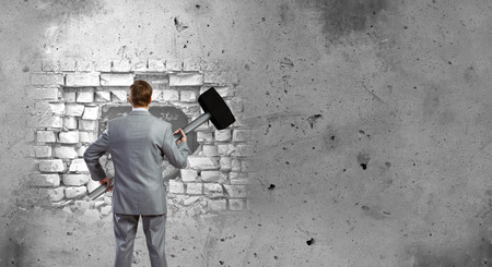 cement solution: Determined businessman with big hammer in hands