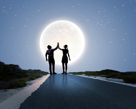 Silhouettes of couple against big moon at background photo