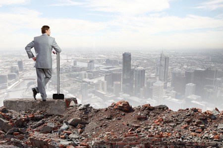 cement solution: Young determined businessman with big hammer in hands standing on ruins Stock Photo
