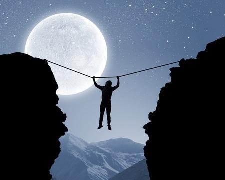 산 간격 위에 로프에 매달려 남자의 실루엣