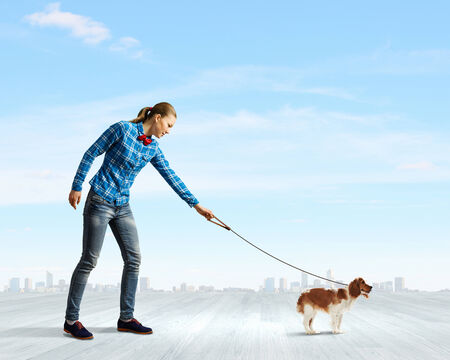 Young woman in casual walking with dog on lead photo